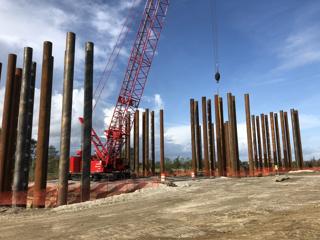 Sets of AMERICAN SpiralWeld steel pipe piles await their turn to be driven deep into the earth to form the subfoundation for a cap-and-pier foundation.